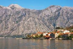 Pequeño pueblo mediterráneo con las casas de piedra con los tejados rojos contra las montañas grises Montenegro, bahía de Kotor Fotografía de archivo
