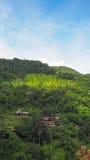 Pequeño pueblo rodeado por las montañas y nateral Foto de archivo libre de regalías