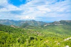 Pequeño pueblo rodeado por los bosques y las montañas Fotografía de archivo libre de regalías