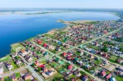 Pequeño pueblo verde hermoso cerca del lago desde arriba Imágenes de archivo libres de regalías