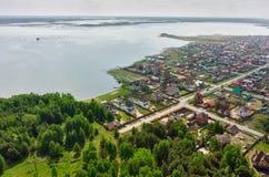 Pequeño pueblo verde hermoso cerca del lago y del bosque Fotos de archivo libres de regalías