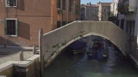 Pequeño puente en un canal en Venecia con el paso del barco almacen de video