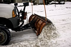 Pequeño quitanieves que quita nieve en una calle de la ciudad Imágenes de archivo libres de regalías