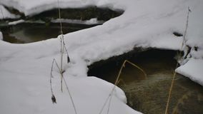 Pequeño río en el invierno y el puente de madera del pueblo almacen de metraje de vídeo