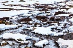 Pequeño río que fluye entre la tierra nevada Fotos de archivo libres de regalías