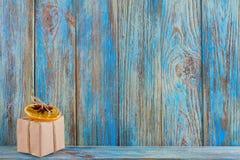 Pequeño regalo adornado con una naranja secada en fondo de madera azul, una tarjeta de felicitación de la plantilla Fotos de archivo libres de regalías