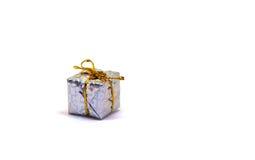 Pequeño regalo de plata en el fondo blanco Caja de regalo de la Navidad en el follaje que envuelve con el arco del hilo del oro Fotos de archivo libres de regalías