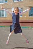 Pequeño salto feliz de la colegiala Imagenes de archivo