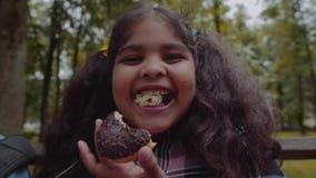 Pequeño schhoolgirl afroamericano divertido que come el buñuelo del chocolate con la emoción feliz en el parque almacen de video