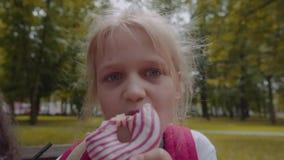 Pequeño schhoolgirl caucásico divertido que come el buñuelo del chocolate con la emoción feliz en el parque almacen de video