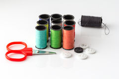 Pequeño Scissor y primer multicolor del fondo de los hilos de coser Imagenes de archivo