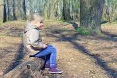 Pequeño sittng rubio caucásico lindo de la muchacha en bosque de madera y la mirada de la clave en alguna parte Niño pensativo ad fotos de archivo