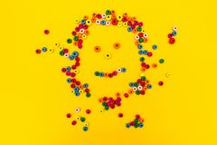 Pequeño smiley sonriente del hombre de los juguetes redondos multicolores en un fondo amarillo imagenes de archivo