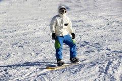 Pequeño snowboarder en el contexto del cielo azul Imágenes de archivo libres de regalías