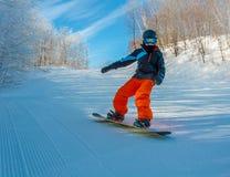 Pequeño snowboarder que va abajo de la montaña Imagenes de archivo