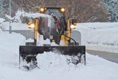 Pequeño snowplow que ara la calzada en nevadas pesadas Imagenes de archivo