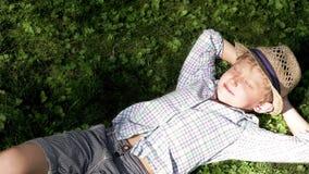 Pequeño tío que miente en la hierba y que se relaja debajo de los rayos solares calientes metrajes