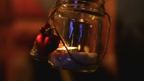 Pequeño tarro adornado con la vela dentro del balanceo en el viento, luz romántica en la noche almacen de metraje de vídeo