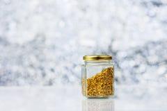 Pequeño tarro con polen de la abeja en fondo borroso Imagen de archivo libre de regalías