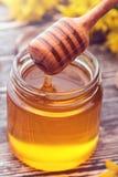 Pequeño tarro de cristal con la miel líquida Imágenes de archivo libres de regalías