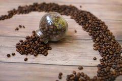Pequeño tarro de cristal del cual se vierten los granos de café Fotografía de archivo