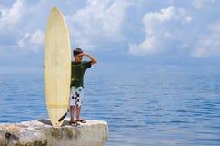 Pequeño tipo de la persona que practica surf del muchacho joven con su tabla hawaiana Fotos de archivo