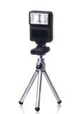 Pequeño trípode con un flash para la cámara aislada encima imagenes de archivo