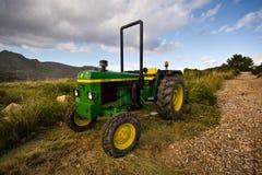 Pequeño tractor verde solo de John Deere cerca del rastro del alza imagen de archivo libre de regalías