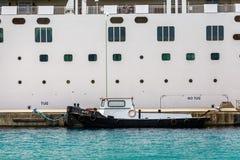 Pequeño Tug Tied al barco de cruceros imagen de archivo libre de regalías