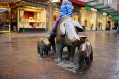 Pequeño turista lindo que se sienta en la escultura popular de la familia del cerdo, del porquero y de su perro en Bremen Fotos de archivo libres de regalías