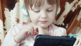 Pequeño vídeo lindo del reloj de la muchacha en la tableta digital almacen de metraje de vídeo