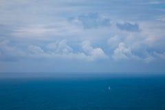Pequeño velero en el océano debajo de un cielo nublado Foto de archivo libre de regalías