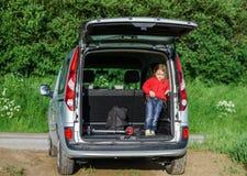 Pequeño viajero en el equipaje del coche Foto de archivo