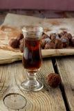 Pequeño vidrio de brandy y de caramelos hechos en casa en la tabla de madera Imagen de archivo libre de regalías
