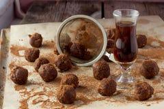 Pequeño vidrio de la tabla de madera del brandy, de la gasa y de los caramelos hechos en casa Foto de archivo