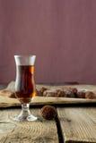Pequeño vidrio de licor y de caramelos hechos en casa en la tabla de madera Imagen de archivo