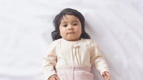 Pequeño viejo bebé de seis meses del afroamericano hermoso en la cama blanca almacen de metraje de vídeo
