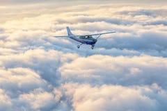 Pequeño vuelo del aeroplano del solo motor en el cielo magnífico de la puesta del sol imagenes de archivo