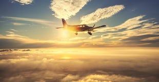 Pequeño vuelo del aeroplano del solo motor en el cielo magnífico de la puesta del sol a través del mar de nubes sobre las montaña fotografía de archivo libre de regalías