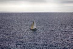 Pequeño yate navegante solo-masted en el fondo de ondas débiles imágenes de archivo libres de regalías