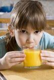 Pequeño zumo de naranja lindo de la bebida de la muchacha Foto de archivo