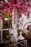 Pequeños ángeles de guarda blancos con las flores rosadas Fotografía de archivo