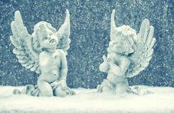 Pequeños ángeles de guarda en nieve Decoración de la Navidad Imagen de archivo libre de regalías