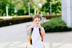 Pequeños 7 años felices de colegial que muestra los pulgares para arriba Foto de archivo libre de regalías