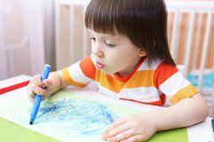 Pequeños 3 años lindos de pinturas del muchacho con las plumas del fieltro Fotografía de archivo
