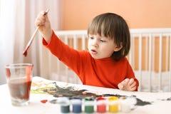 Pequeños 2 años preciosos de muchacho que pinta en casa Foto de archivo libre de regalías