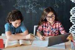 Pequeños alumnos expertos que estudian idiomas en la escuela Imagen de archivo libre de regalías