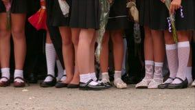 Pequeños alumnos que se colocan en la línea de la escuela