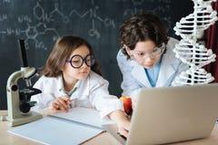 Pequeños amigos implicados que estudian la microbiología en la escuela Foto de archivo libre de regalías