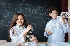 Pequeños amigos positivos que estudian la microbiología en la escuela Foto de archivo libre de regalías